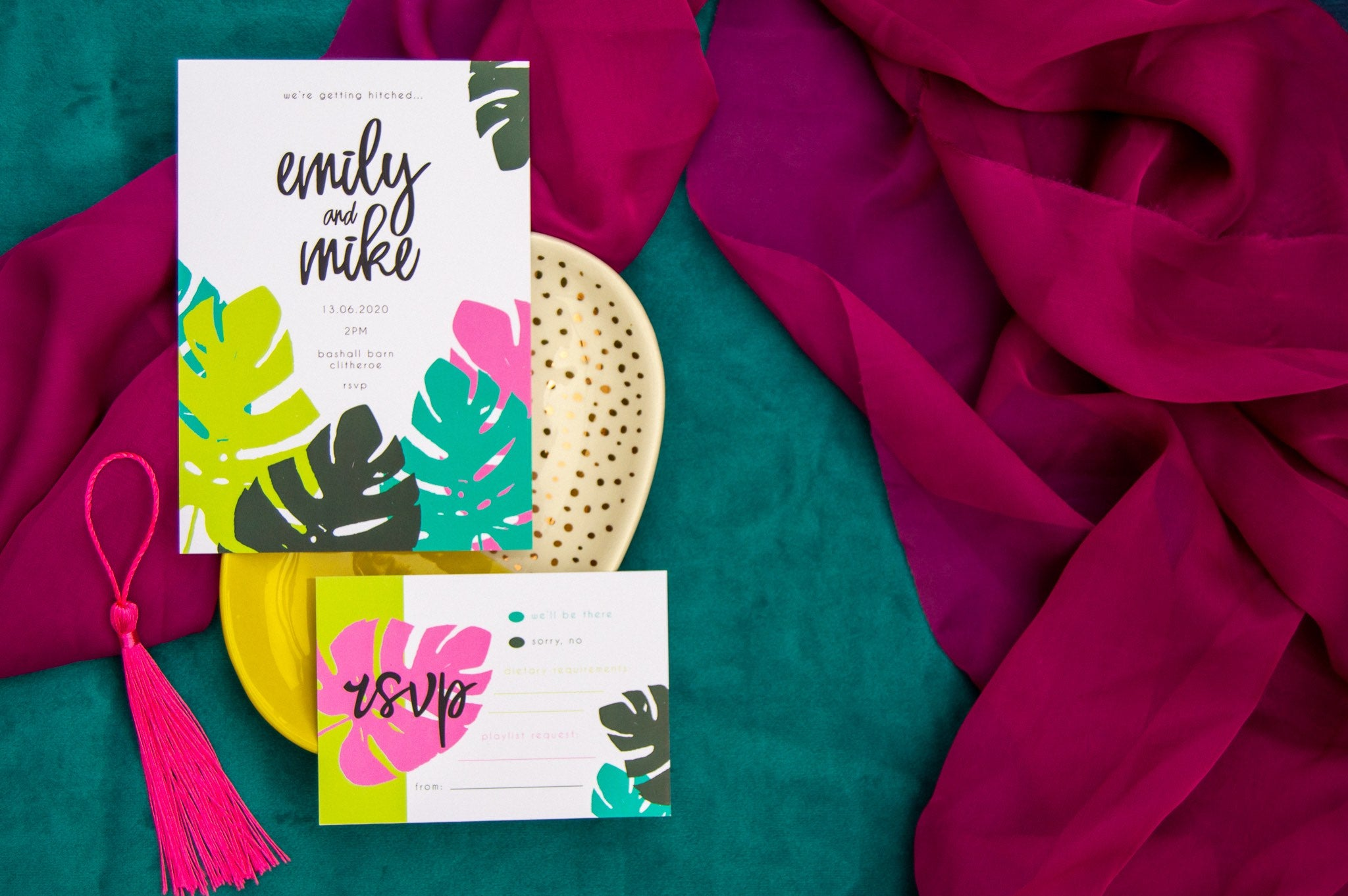 Wedding invitation and RSVP cards to the left of the screen with bold colourful leaf pattern, laid on pink and teal fabric background.