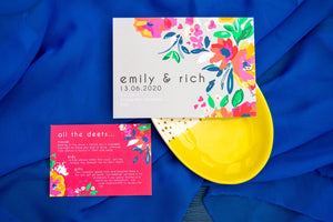 Grey and red wedding invite and details card with bold flower pattern on blue fabric base.