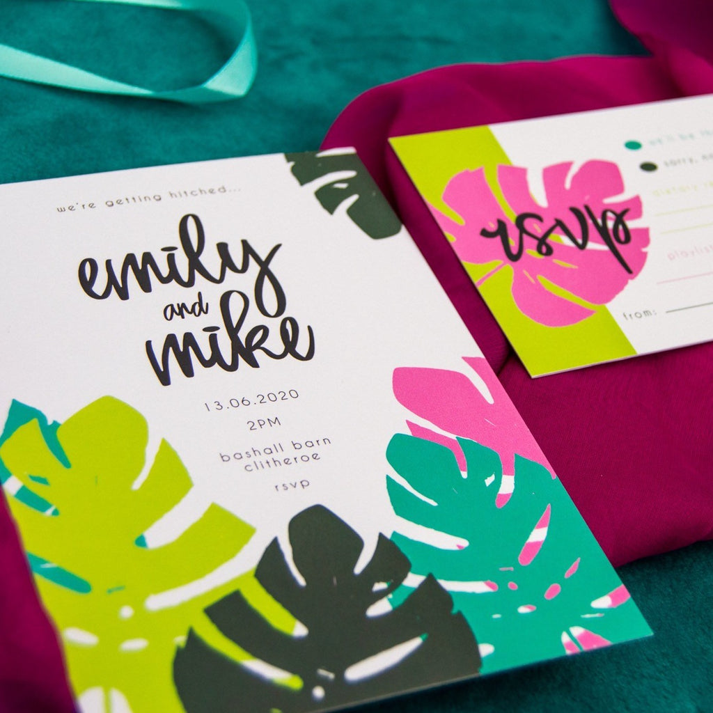 Colourful leaf pattern wedding invitation and RSVP laid on folds of pink and green fabric.