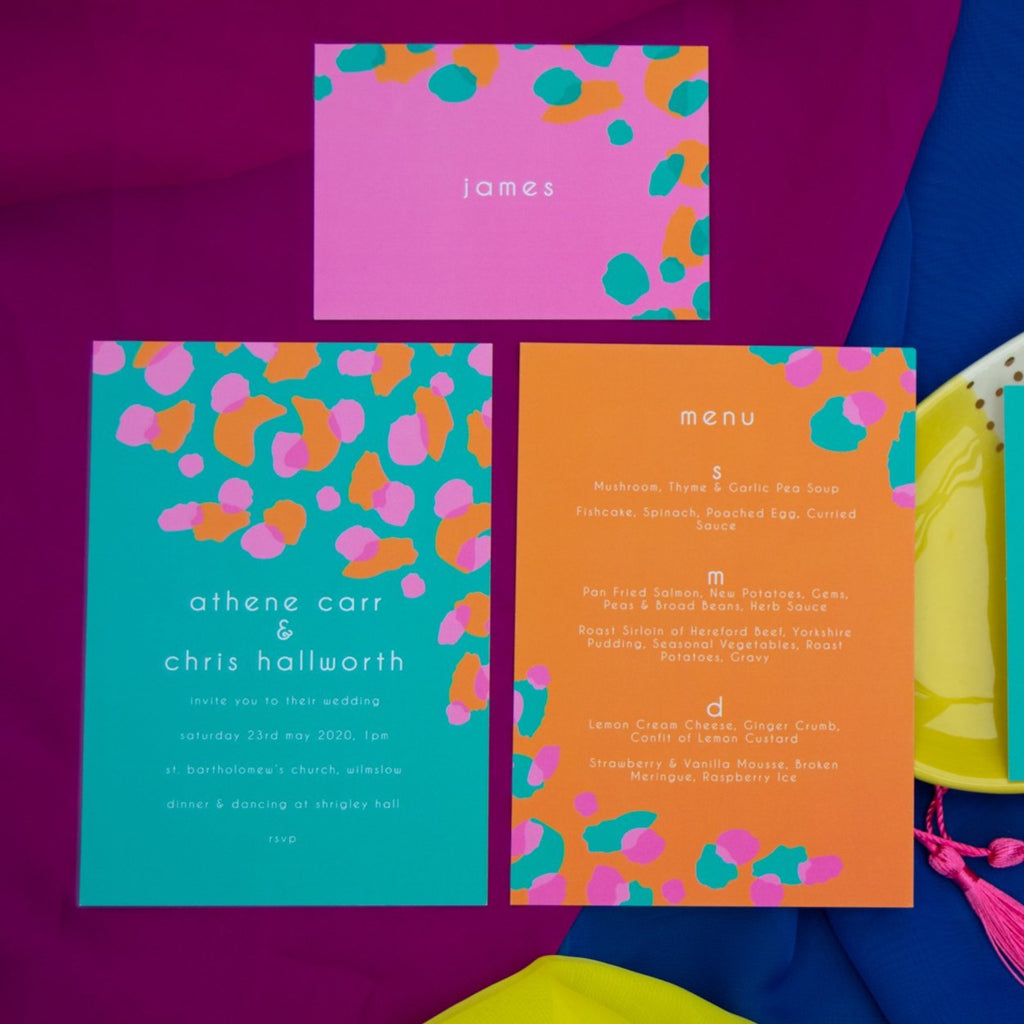 Green, pink and orange leopard print wedding stationery set on blue and purple background.