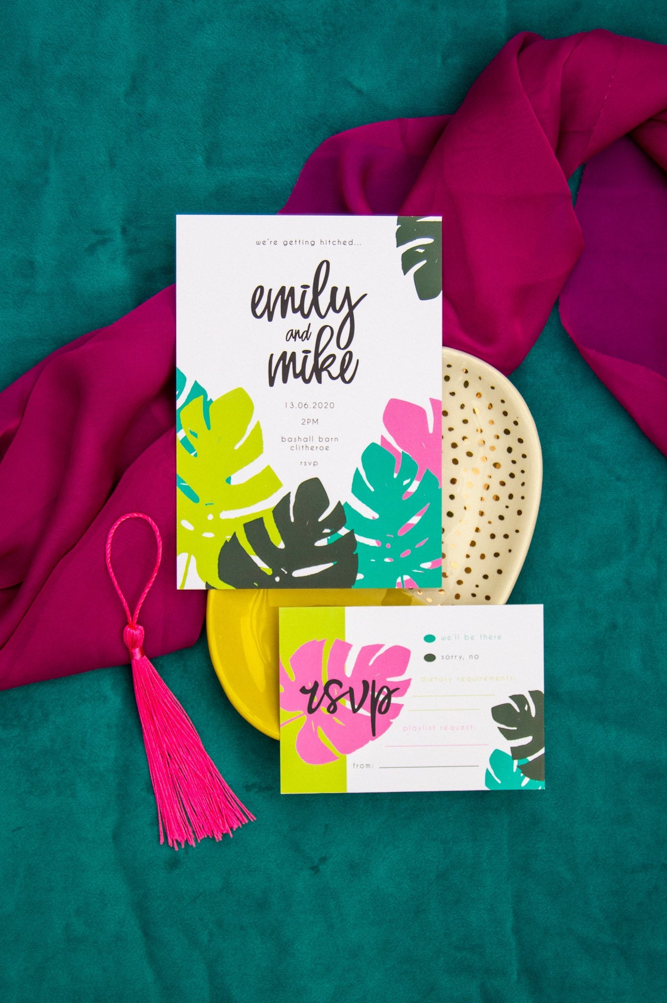 Wedding invitation and RSVP card with green and pink Monstera leave pattern on teal and pink fabric background.