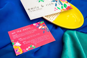 Red wedding invite details card with abstract floral design on green and blue fabric base.