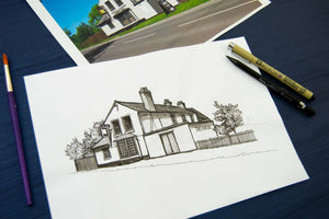 Line drawing of a building on white paper, with paint brush and pens, all laid on a navy background.