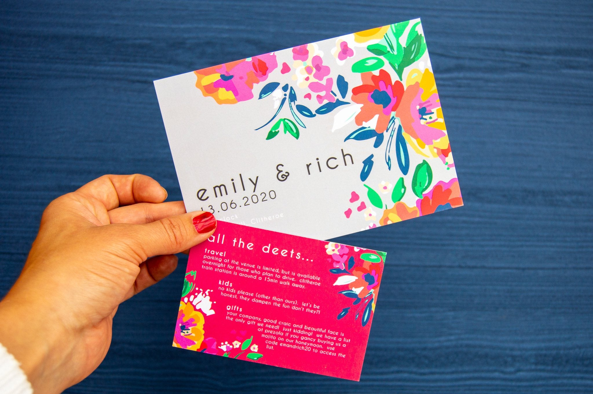 Grey wedding invite and red details card with floral pattern held by a hand over a navy background.
