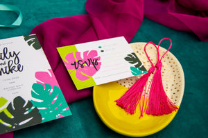Bold tropical inspired wedding RSVP card on green background with pink tassels and yellow plate accessories.