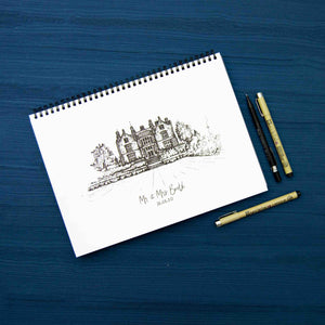 Black and white drawing of a building on a white notepad, laid on a blue background beside pens and a pencil.