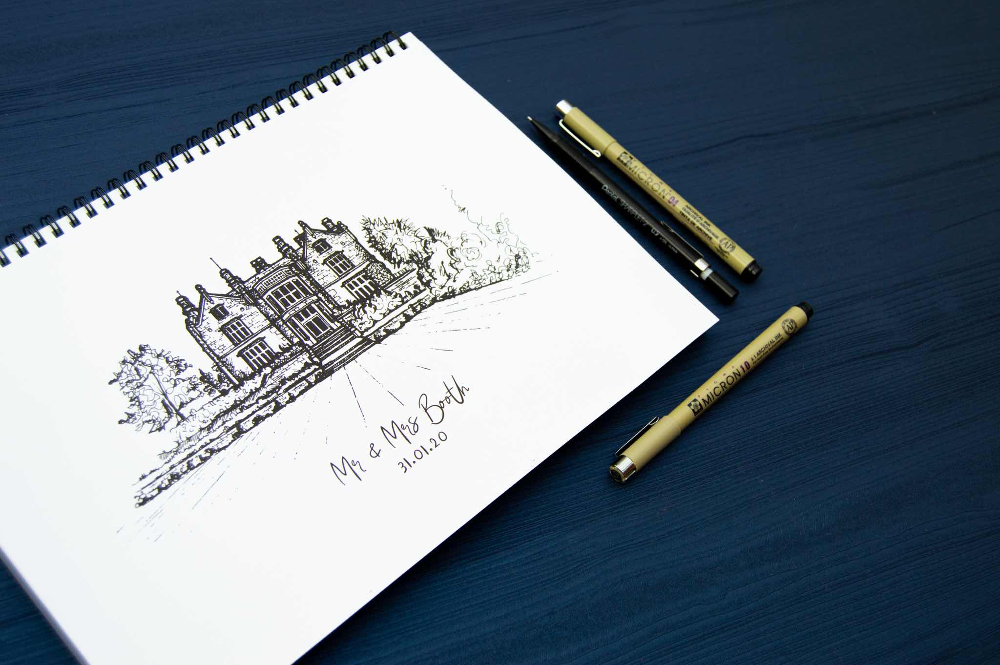 Line drawing of a building on a notepad with pens nearby laid on a dark blue surface.