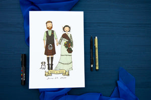 White paper with cartoon drawing of married couple laid on top of blue fabric piece against nave background.