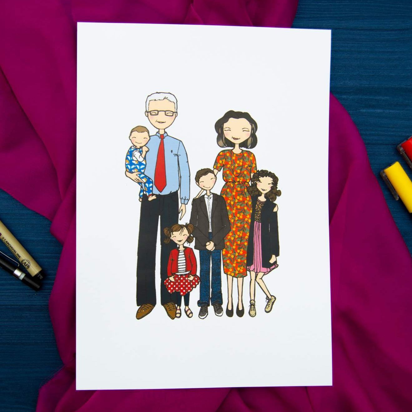 White page with cartoon drawing of family laid on pink fabric background.