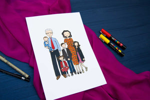 White page with drawing of cartoon family laid on piece of pink fabric against dark blue background.