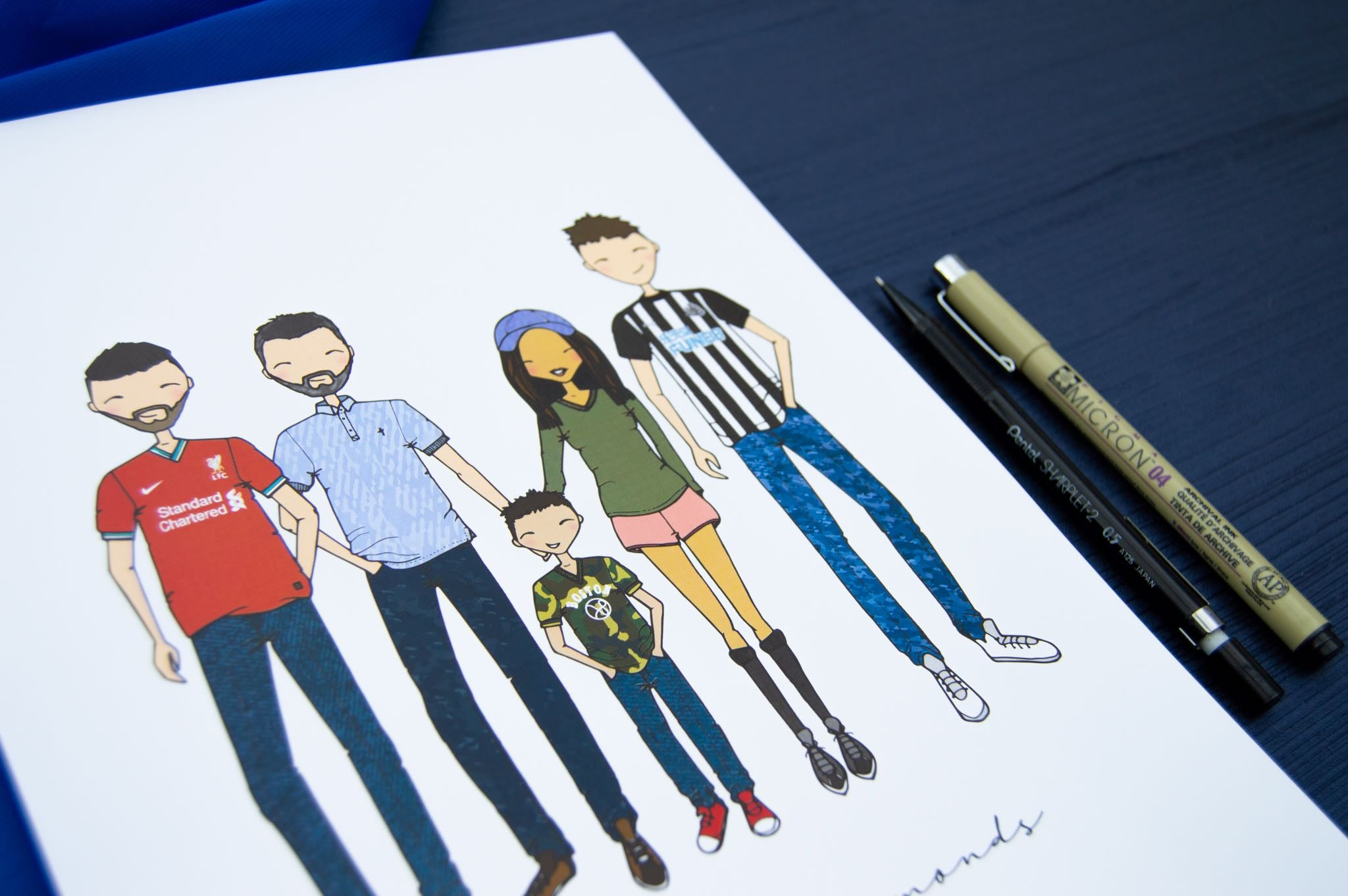 Close up angled shot of cartoon family drawing on white paper with blue background.