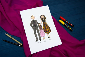 Family cartoon drawing on white paper with pens to the side laid on pink fabric background.