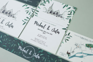 White wedding invitation with dark green accents and foliage details, hand drawn venue illustration, laid on pale green surface.