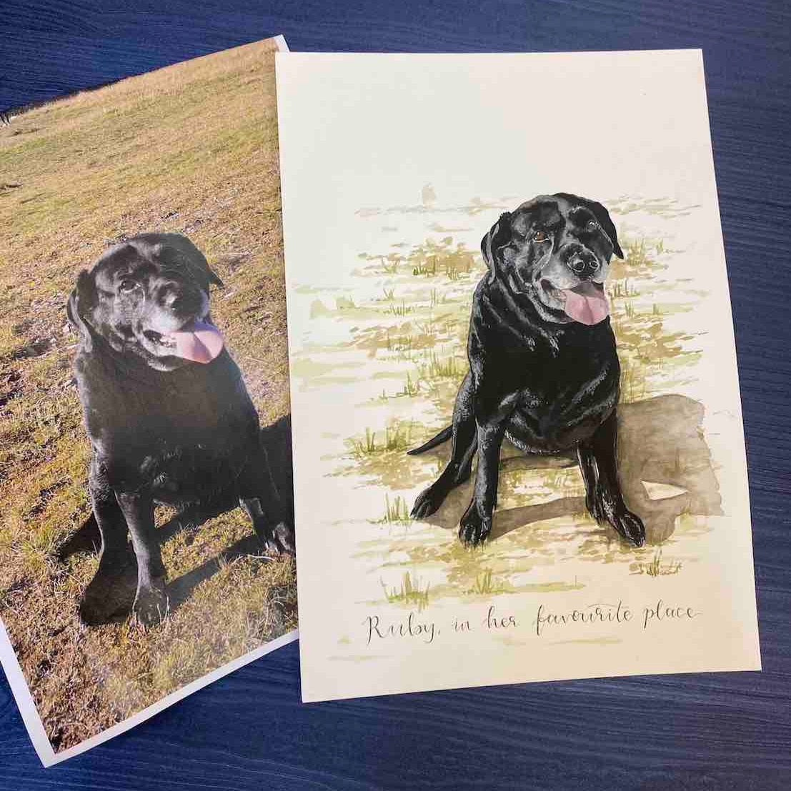 Detailed painting of black Labrador alongside original photo reference of the same dog, both pages are laid on a dark blue background.