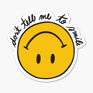 Upside down, yellow, cartoon smiley face. Text around top reads: don't tell me to smile.