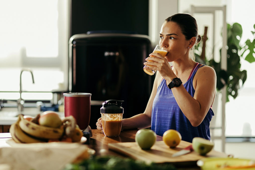 Young athletic woman drinking fruit smoothie in the kitchen