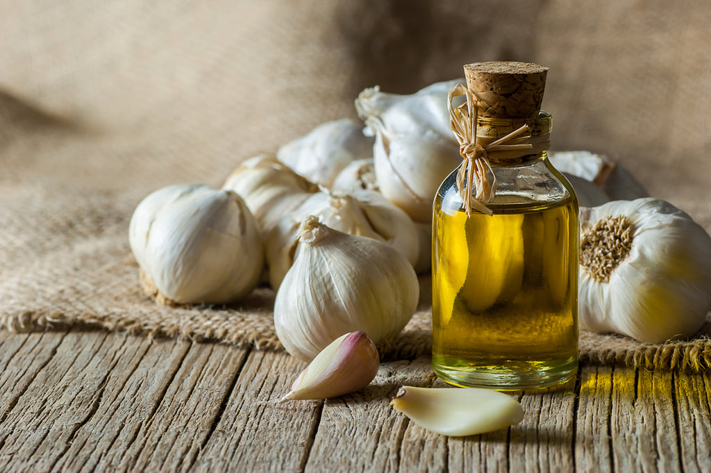 Ripe and raw garlic and garlic oil in glass of bottle on wooden table with burlap sack