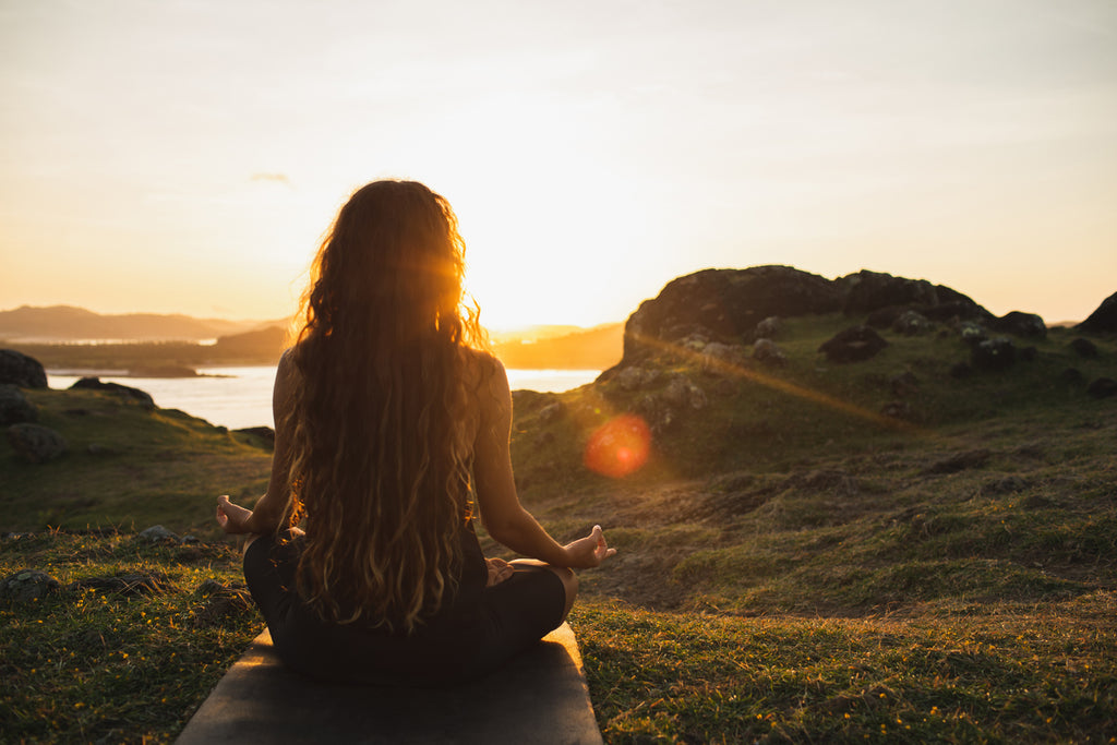Woman meditating yoga alone at sunrise mountains. View from behind. Travel Lifestyle spiritual relaxation concept. Harmony with nature.