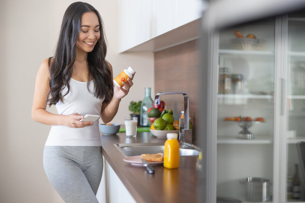 Woman with a dietary supplement in the kitchen