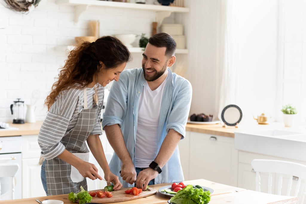 Couple preparing together vegetable salad standing in kitchen at home