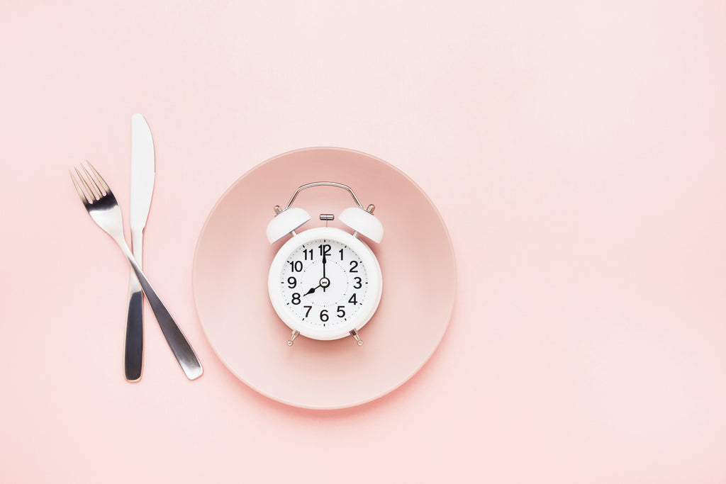 Intermittent fasting concept. White alarm clock on empty pink dish with knife and fork on pink background