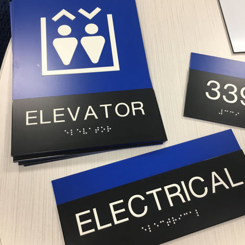 Unique ADA signs for restrooms, exits, rooms and more with bold blue, black and white with high-contrast, tactile printing that's fully-compliant with ADA regulations - NapADASigns.com