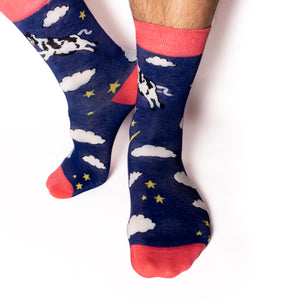 Just like in the nursery rhyme when the cow jumped over the moon. A navy base sets the scene of a fantastical, fun, star-filled night sky. Cows. On Socks. We know!  Available in US Men's 4-8 and 8-12. Soft. Strong. Sustainable. Comfortable. Incredible Socks. Cow jumping over the moon socks.