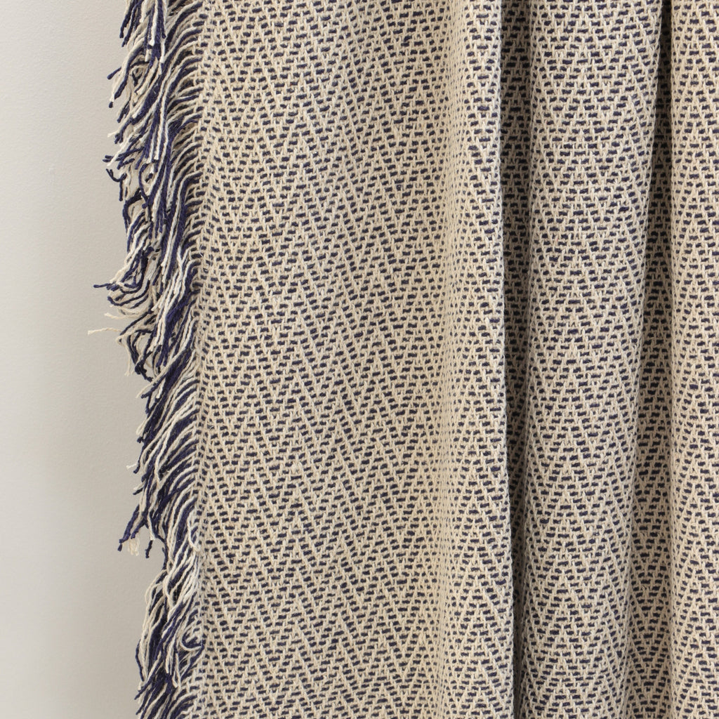 Jasper cotton throw in Navy, herringbone weave and fringed trim detail.