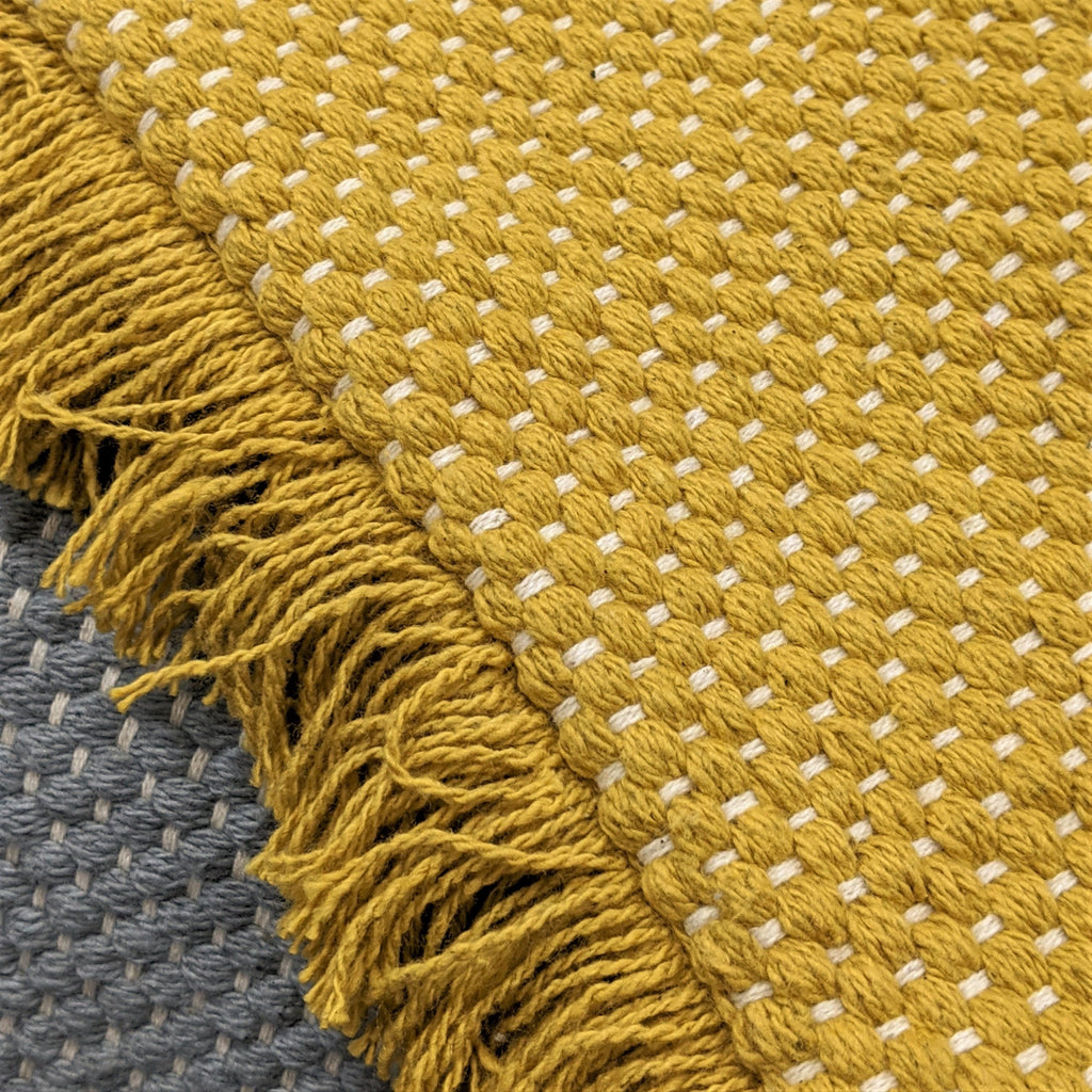 Sienna cushion in ochre, detail of woven texture and fringed trim