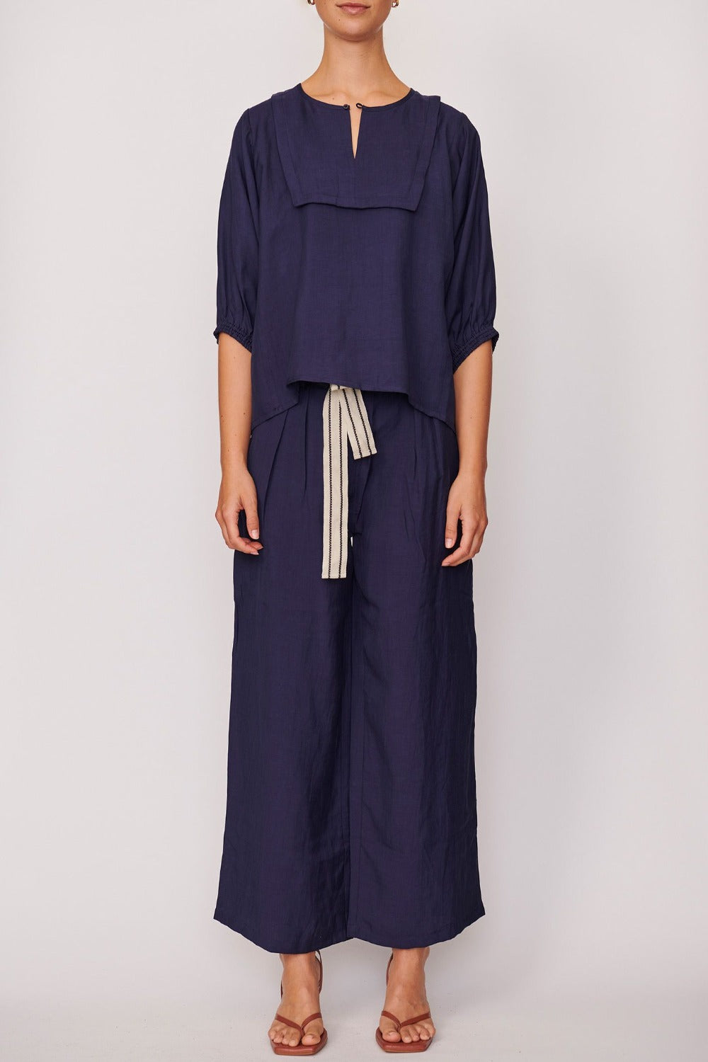 35% linen, 20% rayon, 45% polyester . Fixed waistband with belt loops, hip and back pockets, pleats at the centre front of each leg, a wide leg fit