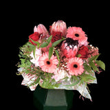 A perfectly pink arrangement designed with a colour combination of soft pinks, daring reds and an accent of soft foliage. Teresa Brough Designer Florist, Takaka NZ