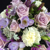 Enjoy this group of mauve roses, freesias and carnations