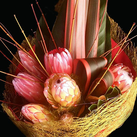 A contemporary design of proteas and decorative wooded stems are wrapped in a naturalistic weave.