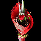 single beautifully wrapped red rose is garnished with greenery and a light spray. Teresa Brough Designer Florist, Takaka NZ