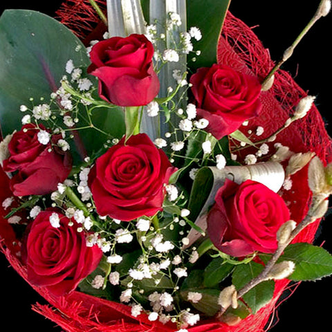 A classic bouquet with six beautifully wrapped red roses garnished with greenery and a light spray.