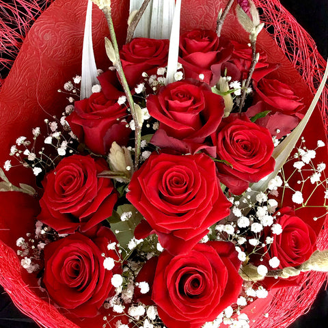 An absolute classic bouquet with a dozen beautifully wrapped red roses garnished with greenery and a light spray.