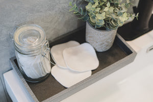 Decorative tray with white organic bamboo facial rounds on bathroom vanity
