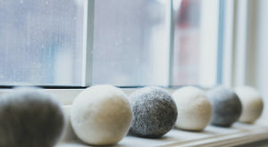 Alternating grey and white wool dryer balls on window sill