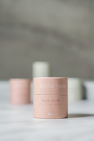 A pink paper-based tube labelled as a Face Stick from the brand Bottle None. The stick is displayed on a white surface, with 3 other pink and green tubes blurred in the background.