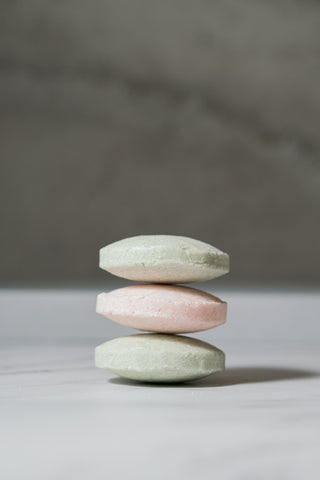 A stack of three face wash bars in alternating colours of mint green and pink, on a white surface in front of a concrete background.