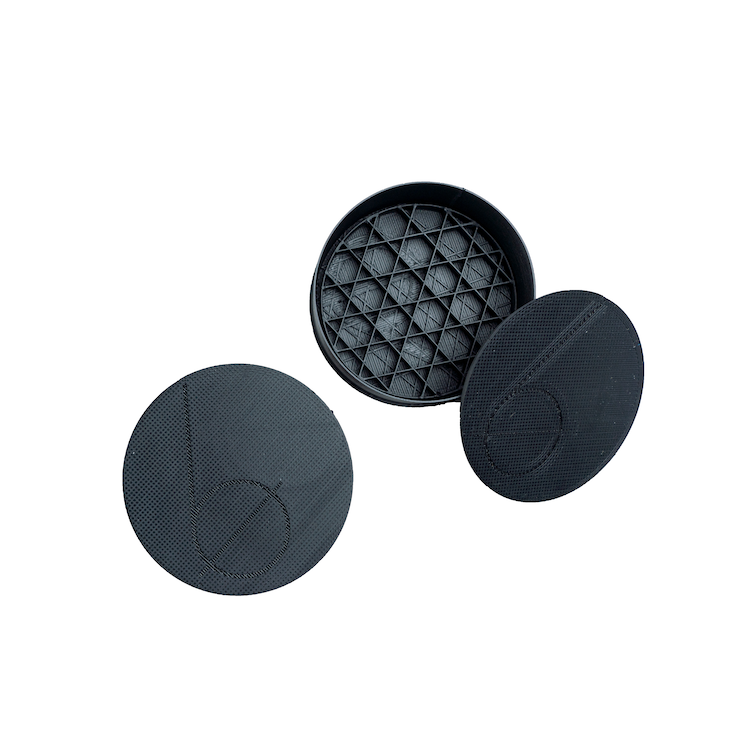 Two black round plastic cases with Bottle None's logo (a large b) on the top. One case is closed and the other case is opened showing the inside of the case with a geometric inner tray.