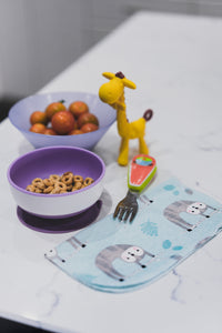Cheerios and cherry tomatoes in children's bowls with fork, toy giraffe and printed cotton napkin