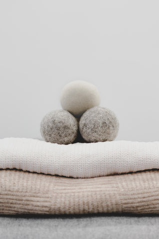 Two grey and one ivory wool dryer ball sitting on folded pile of sweaters
