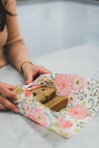 Woman wrapping sliced raisin bread in beeswax food wrap