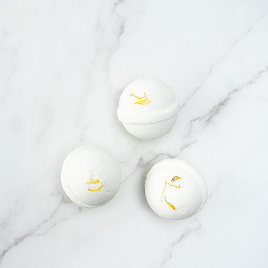Three white coloured bath bombs with yellow dried calendula petals on top, displayed on a marble surface.