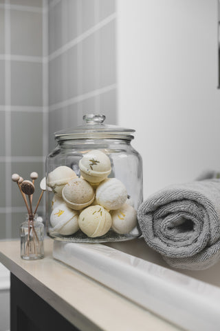 A large glass jar filled with bath bombs sitting on the edge of the sink in the bathroom, beside a rolled up grey towel and decorative accessories on the sink.