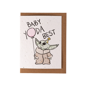 "A white greeting card laying over top of a kraft envelope. The card contains an image of Yoda holding a pink balloon wearing a birthday hat, with text ""Baby Yoda Best"""