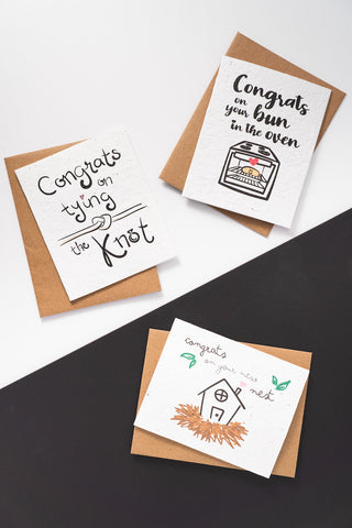Three congratulatory greeting cards with their respective kraft envelopes laid out on a black and white background.
