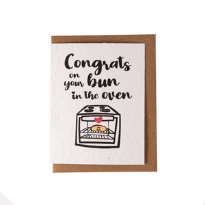 "A white greeting card laying over top of a kraft envelope. The card contains an image of a small oven with a bun inside, with text ""Congrats on your Bun in the Oven"""