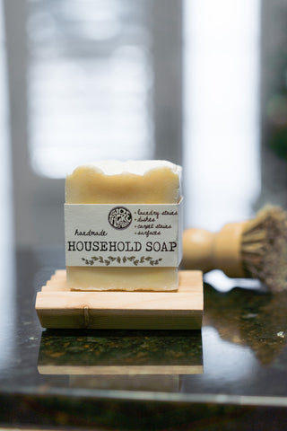 Two Acre Farm's household soap on a soap dish sitting on a kitchen counter with a dish scrub brush